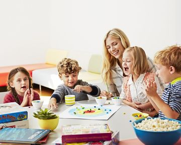 Mom and 4 Children Playing Board Game