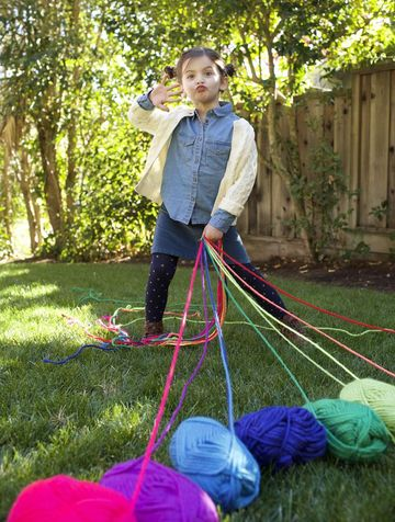 girl holding colorful string making funny face