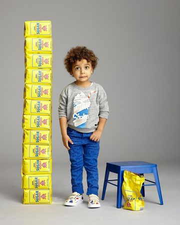 Curly Haired Boy Next to Bags of Sugar