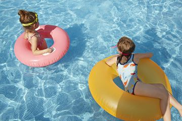 Two Girls On Float Tubes in Pool