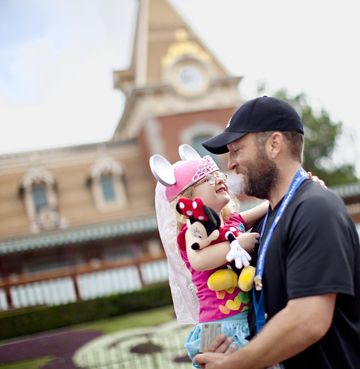 Disney Theme Park Price Father Holding Daughter with Souvenirs