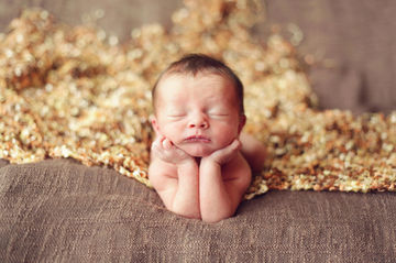 newborn baby with head in hands and eyes closed