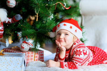 Child under the Christmas tree in Santa hat