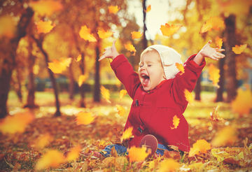 toddler playing in leaves