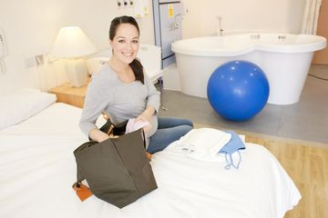 Pregnant woman unpacking in her room at a birthing center
