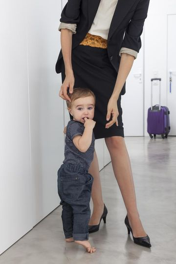 Working mom with baby and suitcase Getty