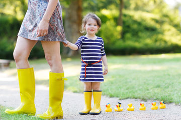 Girl Wearing Yellow Rain Boots Tugging at Moms Dress