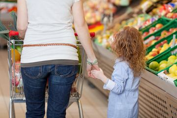mom holding daughter's hand in grocery store