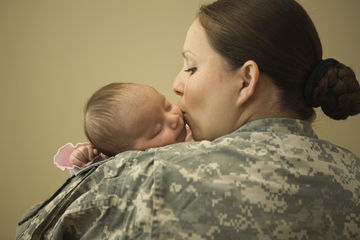 military mom kissing newborn baby