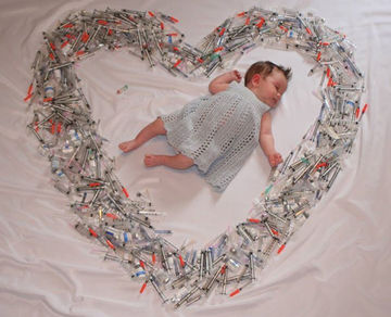 baby surrounded by IVF needles