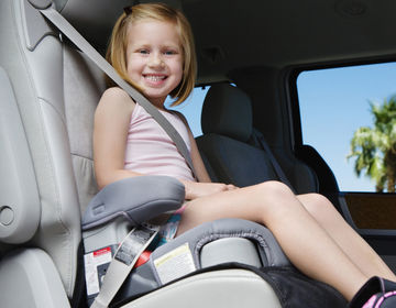 young girl in car booster seat