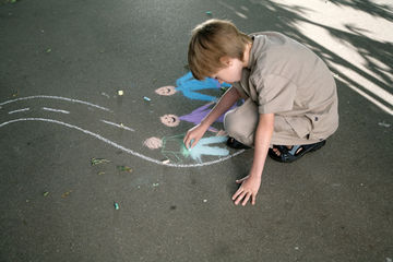 boy drawing with chalk on the street