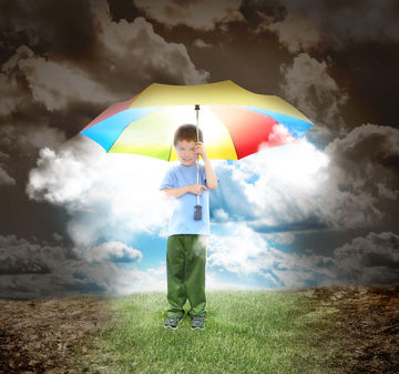 boy standing under a colorful umbrella