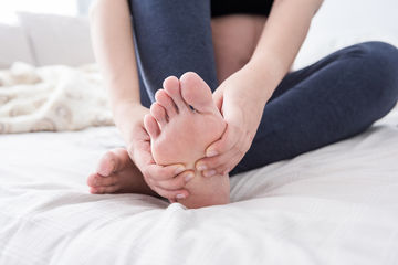 Woman on Bed Rubbing Her Foot