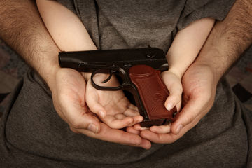 child and father holding gun