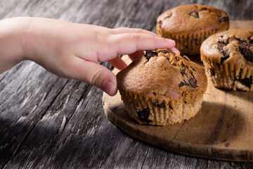 Child Reaching for Second Helping of Muffins