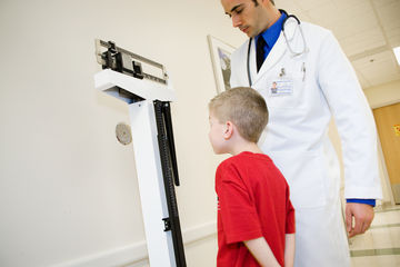 child being weighed by doctor