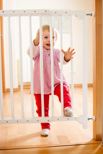 Little Girl in Pink Shirt Behind Baby Gates