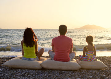 family meditating on the beach while looking out at the ocean