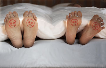 Couple in bed with sad faces drawn on feet