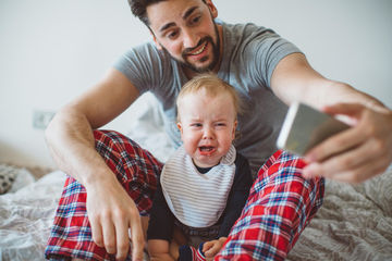 dad taking picture of crying baby