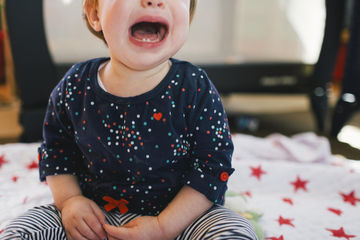 Toddler girl sitting on the floor crying