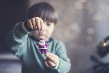 Holiday traditions: Child holding Christmas ornament