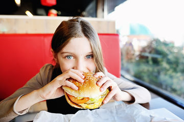 Girl eating burger in restaurant