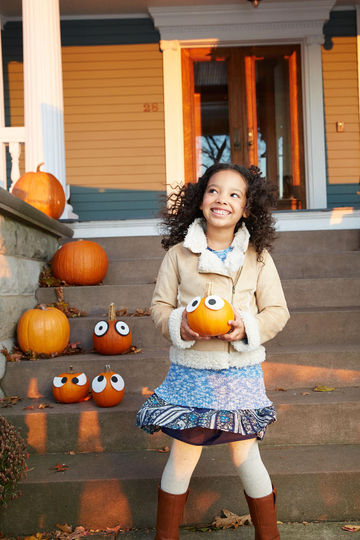 Girl on porch holding pumpkin with eyes