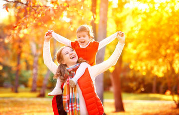 happy mom carrying daughter on shoulders outside in fall
