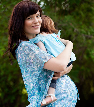 happy pregnant mom wearing blue and holding baby