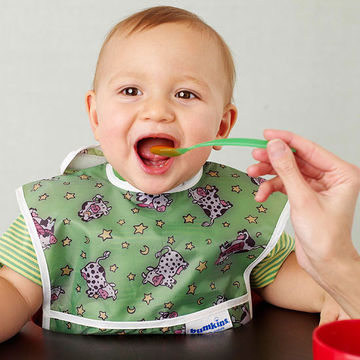 Baby in high chair being fed with a spoon