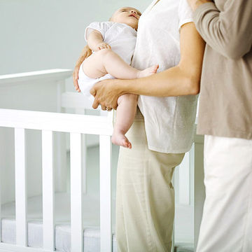 parents putting baby to bed