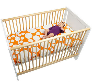 Crib with orange sheet that has cream dots