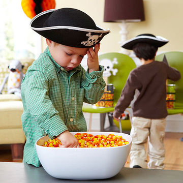 child with hand in candy bowl