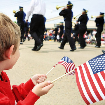 Boy holding American flags and watching parade