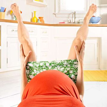 Woman giving birth in kitchen