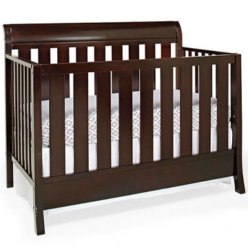 wood crib with white patterned sheet