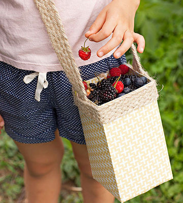 child holding basket of berries