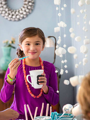 Girl in purple and hanging snowfall craft