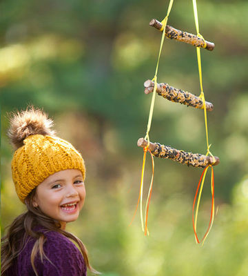 Girl and three-tied stick bird feeder