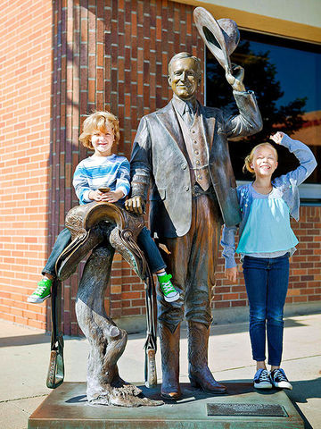 2 kids with Calvin Coolidge and saddle statue