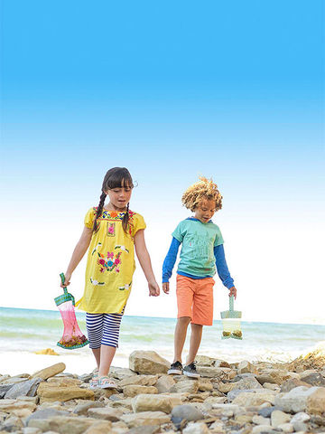 Boy and girl walking on beach holding Explorer's Bags