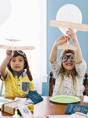 Girl and boy flying balsa wood airplanes
