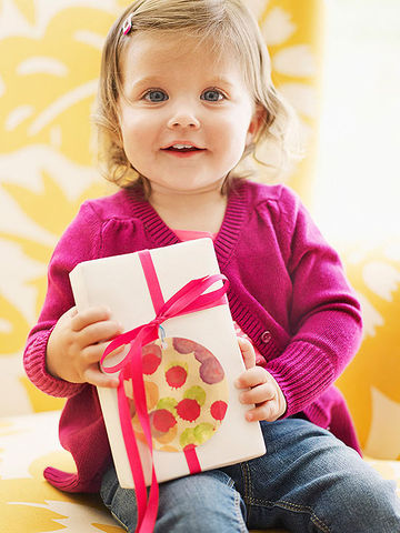Girl in pink sweater holding present with Artful Gift Tag