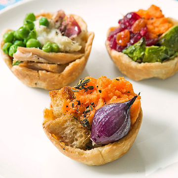 Three bite-sized pot-pies with veggies, turkey and stuffing toppings on white plate