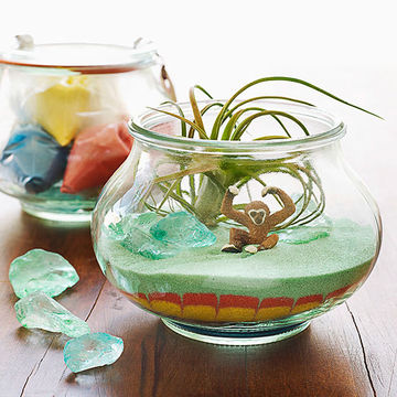 Painted desert terrarium with plastic monkey figure inside