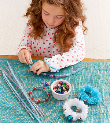 Girl making bead bracelets atop table with blue covering