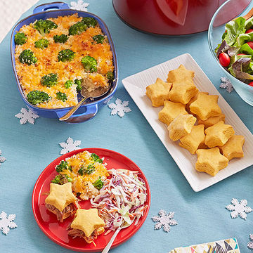 Table of food with blue dish of broccoli casserole, white rectangular plate of star-shaped biscuits, and red plate of food