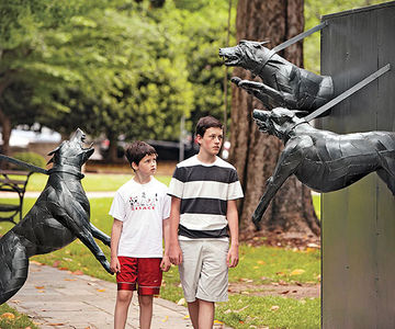 Boys walking between dog statues